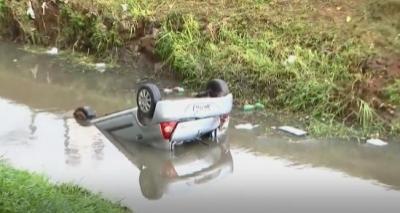 Carro capota em pista molhada, cai em córrego e deixa dois feridos no Rio Vermelho
