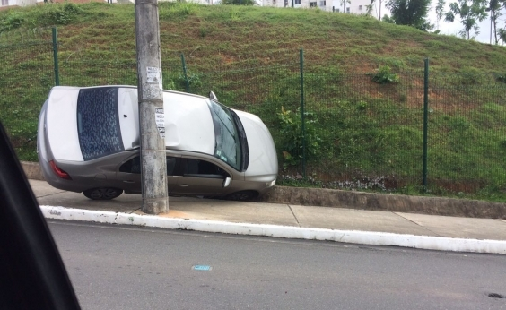 Carro sobe em passeio e fica preso entre poste e colina