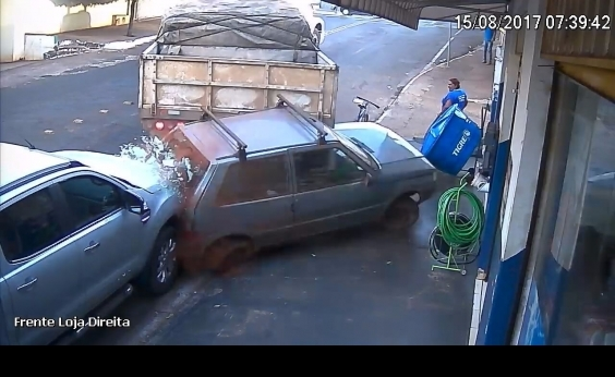 Carreta desgovernada desce rua de ré, arrasta carro e invade loja; veja vídeo