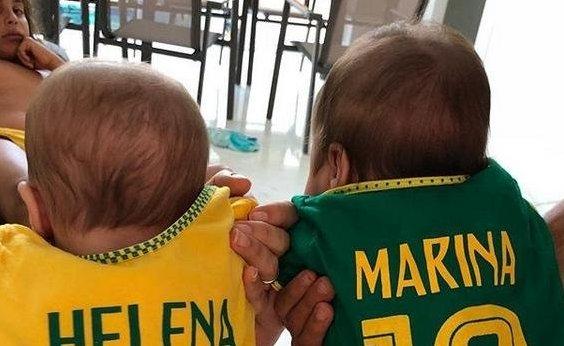 [Ivete veste gêmeas com camisa personalizada da seleção e Marcelo aparece com cara de ciúmes]