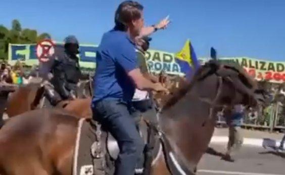 [Montado em cavalo, Bolsonaro cumprimenta apoiadores em manifestação]
